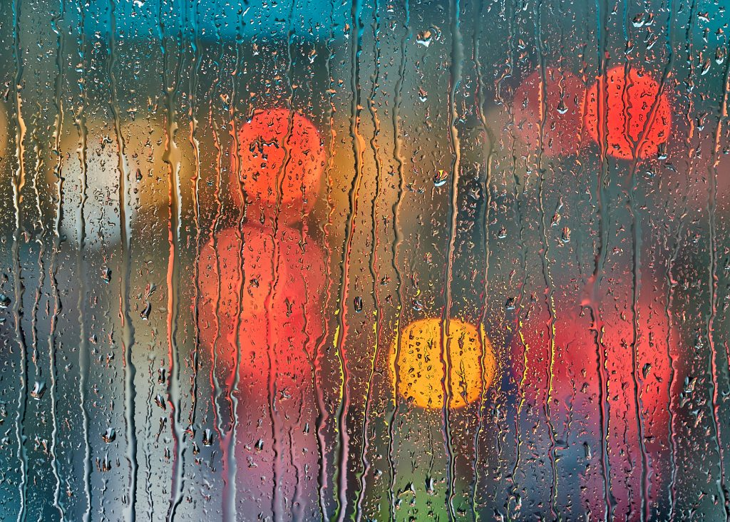 Street lights and traffic, through rainy glass in a Minneapolis skyway.