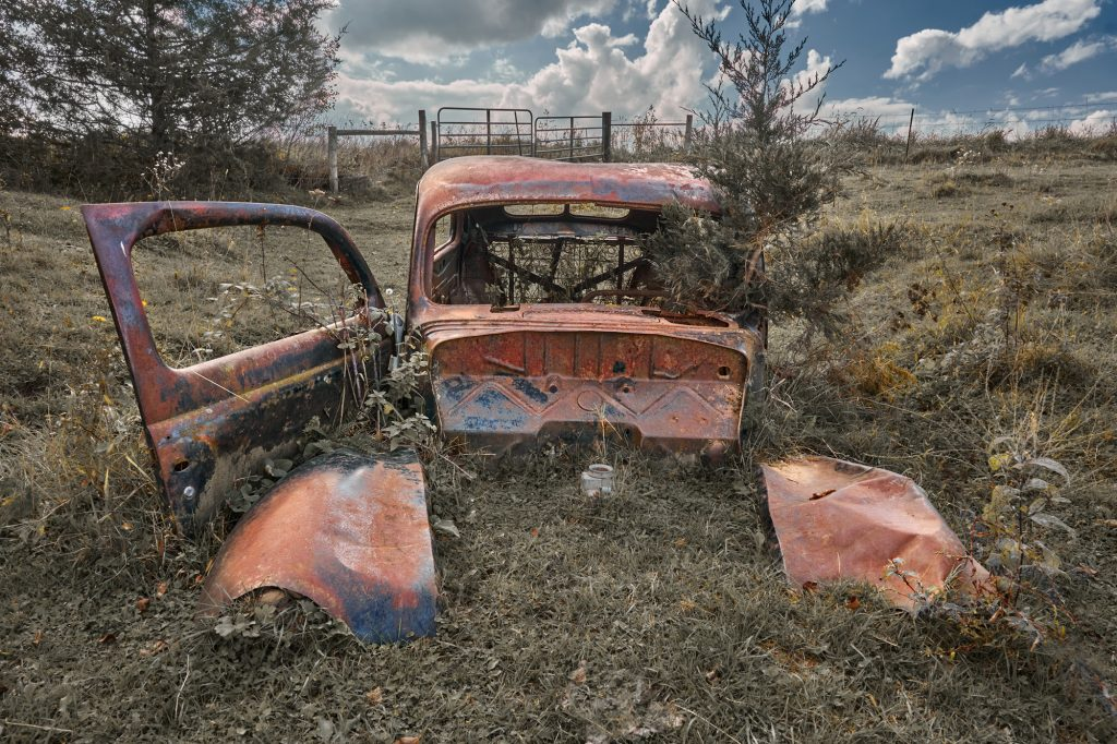 An old Ford rusts peacefully in a farmer's field.